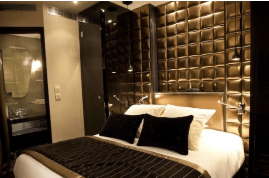 A Gold and White Bed with High-gloss Black Walls