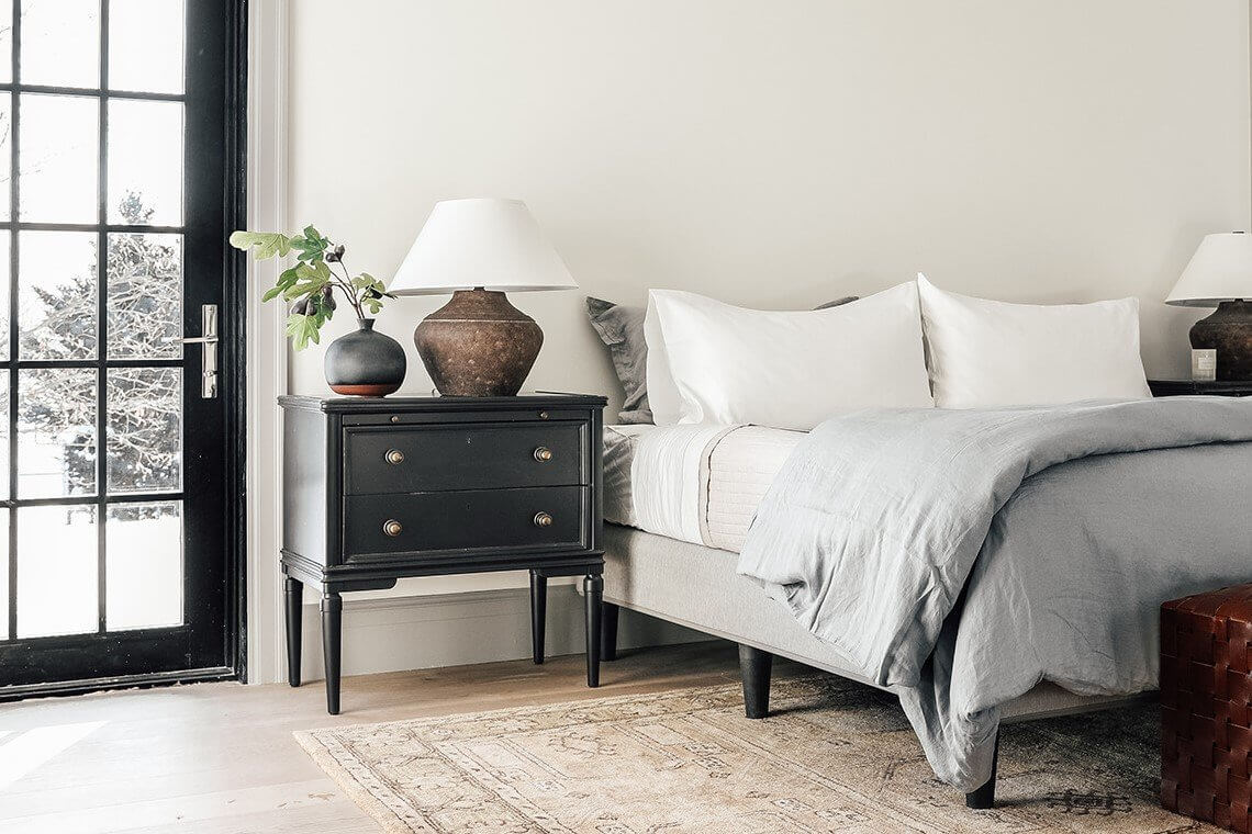 white bedroom with black nightstand